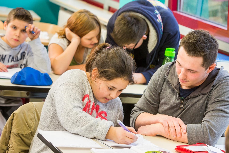 Eine Schülerin mit Kopftuch unterhält sich mit einem Schüler, der einen Hut trägt